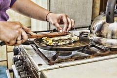 Eine Frau bereitet Frühstück zu Hause in der Küche zu Toast in einer Bratpfanne mit Eigrün und -speck Gesunde Nahrung Lizenzfreie Stockfotos