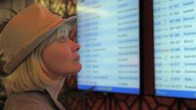 Eine Frau betrachtet das Informationsbrett von Abfahrt auf den Flughafen stock footage