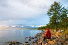 Eine Frau betrachtet den See Hovsgol im Sonnenunterganglicht Höchst-Munku-Sardyk - nahe der Mitte des Rahmens auf dem links mongo Lizenzfreies Stockfoto