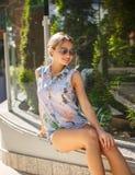 Eine Frau in den Denimkurzen hosen und im bunten Hemd Stockfotografie