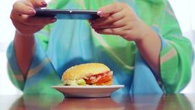 Eine Frau in den Fotografien eines Cafés am Telefon ein Burger stock footage