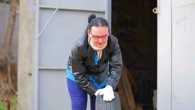 Eine Frau in den Gl?sern stellt einen Autoreifen mit einer Diskette aus der Garage heraus bereit stock video footage