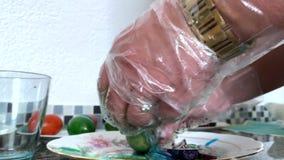 Eine Frau in den Handschuhen malt Eier stock video