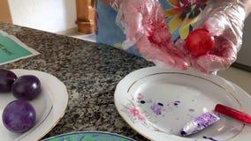 Eine Frau in den Handschuhen malt Eier stock video footage