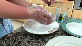 Eine Frau in den Handschuhen malt Eier stock footage