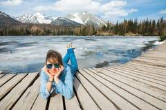 Eine Frau in den Jeans, die auf h?lzerner Terrasse durch gefrorenes Gebirgslak liegen lizenzfreie stockfotos