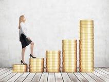 Eine Frau in der Abendtoilette geht aufbrauchen Treppe, die von den goldenen Münzen hergestellt werden Ein Konzept des Erfolgs Lizenzfreie Stockbilder