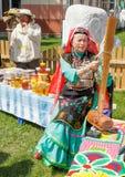 Eine Frau in der Bashkir Kleidung ist, spinnend sitzend und Wolle Traditioneller Nationalfeiertag Sabantuy im Stadtpark stockfotografie
