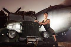 Eine Frau in der Militärkleidung, die nahe einem Flugzeug aufwirft Lizenzfreies Stockfoto
