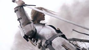 Eine Frau in der mittelalterlichen Rüstung lehnt sich auf ihrer Klinge und beugt ihren Kopf stock video