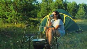 Eine Frau in der Sonnenbrille nahe einem trinkenden Tee und dem Bewundern des Feuers der Natur stock footage