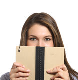 Eine Frau, die über einem Anmerkungsbuch im Studio schaut Lizenzfreie Stockfotografie