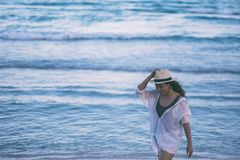 Eine Frau, die auf den Strand schlendert stockfotografie