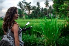 Eine Frau, die auf einem Fahrrad nahe fantastischer Landschaft, Dschungel, tropischem Wald vor ihr und der Natur sitzt Konzept vo stockbild