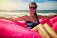 Eine Frau, die auf einem rosa Luftboot auf dem Strand sitzt lizenzfreie stockfotografie