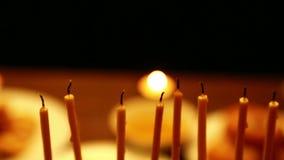 Eine Frau, die auf einer brennenden Kerze durchbrennt, die in einem Kerzenständer ist Nahaufnahme