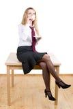 Eine Frau, die auf einer Tabelle sitzt Lizenzfreie Stockbilder