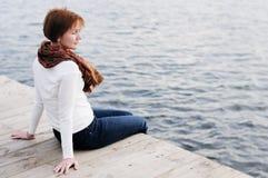 Eine Frau, die auf hölzernen Vorständen sitzt Stockfoto