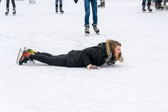 Eine Frau, die auf ihrem Magen auf dem Eis liegt, wenn Sie draußen an einer allgemeinen Eislaufeisbahn eislaufen Lizenzfreie Stockbilder