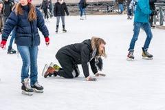 Eine Frau, die auf ihren Knien auf dem Eis liegt, wenn Sie draußen an einer allgemeinen Eislaufeisbahn eislaufen Stockfotos