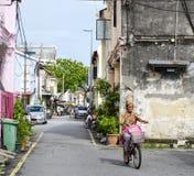 Eine Frau, die auf Straße in Penang, Malaysia radfährt Lizenzfreies Stockbild