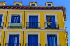 Eine Frau, die aus dem Balkon eines Blockes der Wohnungen heraus schaut Stockbild