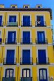 Eine Frau, die aus dem Balkon eines Blockes der Wohnungen heraus schaut Stockfoto