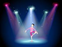 Eine Frau, die Ballett auf dem Stadium mit Scheinwerfern durchführt Lizenzfreie Stockbilder