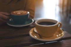 Eine Frau, die eine blaue Schale heißen Kaffee und eine andere gelbe Schale auf Tabelle im Café hält Lizenzfreie Stockfotos