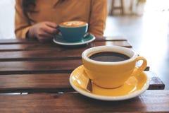 Eine Frau, die eine blaue Schale heißen Kaffee und eine andere gelbe Schale auf Tabelle im Café hält Lizenzfreies Stockbild