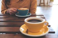 Eine Frau, die eine blaue Schale heißen Kaffee und eine andere gelbe Schale auf Tabelle im Café hält Lizenzfreie Stockbilder