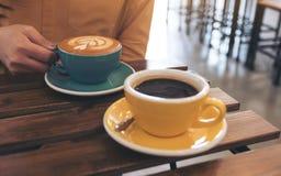 Eine Frau, die eine blaue Schale heißen Kaffee und eine andere gelbe Schale auf Tabelle im Café hält Stockfotos