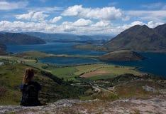 Eine Frau, die den See Wanaka nahe der Stadt Wanaka in Neuseeland sitzt und betrachtet lizenzfreies stockbild
