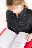 Eine Frau, die durch ein rotes Faltblatt schaut Lizenzfreie Stockfotos
