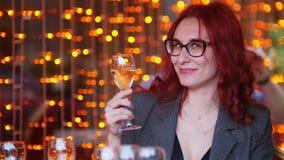 Eine Frau, die durch Tabelle im Restaurant und in trinkendem Champagner sitzt stock video footage