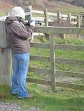 Eine Frau, die ein Foto auf einem Gebiet macht lizenzfreie stockbilder