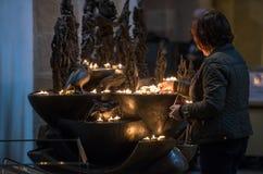 Eine Frau, die eine Kerze in Speyer-Kathedrale, Deutschland setzt Stockbilder
