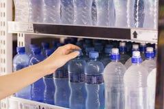 Eine Frau, die eine Wasserflasche nimmt Stockfotos