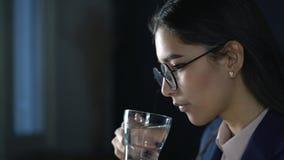 Eine Frau, die an einem Laptop im Büro arbeitet Getränktrinkwasser stock video footage