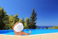 Eine Frau, die in einem Swimmingpool mit Cocktail sich entspannt stockfotografie