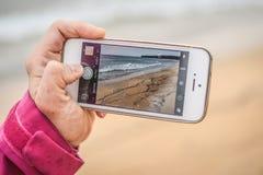Eine Frau, die einen isländischen Strand des Telefons mit sandiger Küste a fotografiert Stockfotografie