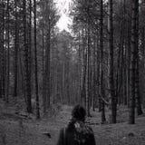 Eine Frau, die einen Waldweg mit ihr zurück zu der Kamera betrachtet stockfotografie
