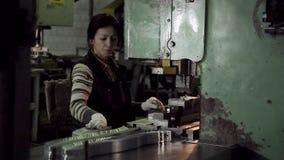 Eine Frau, die an einer Maschine für die Formung von Befestigern sitzt stock video footage