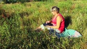Eine Frau, die in einer Wiese mit einem Laptop arbeitet stock video