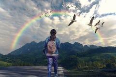 Eine Frau, die entlang den Weg zum Berg geht stockfotos
