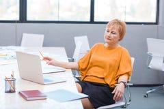 Eine Frau, die für einen Laptop sitzt im Büro interessiert schaut Lizenzfreie Stockbilder