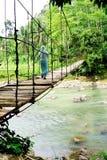 Eine Frau, die eine hängende Brücke kreuzt stockbild
