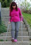 Eine Frau, die hinunter ein Treppenhaus mit Krücken geht lizenzfreies stockfoto