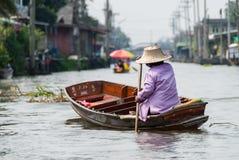 Eine Frau, die hinunter einen Kanal in Thailand schwimmt stockfotografie
