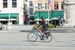 Eine Frau, die ihr Fahrrad fährt Lizenzfreie Stockbilder